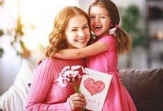 Happy mother`s day! child daughter gives mother a bouquet of flowers and postcard. Happy mother`s day! child daughter congratulates mother and gives a bouquet of royalty free stock images