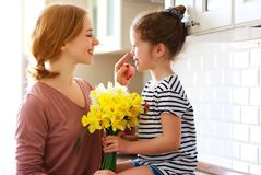 Happy mother`s day! child daughter   gives mother a bouquet of flowers to narcissus and gift. Happy mother`s day! child daughter congratulates mother and gives a stock photo