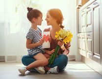 Happy mother`s day! child daughter   gives mother a bouquet of flowers to narcissus and gift. Happy mother`s day! child daughter congratulates mother and gives a royalty free stock photos