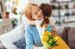 Happy mother`s day! child daughter gives mother a bouquet of flowers to tulip and gift. Happy mother`s day! child daughter congratulates mother and gives a royalty free stock photos