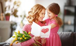 Happy mother`s day! child daughter gives mother a bouquet of flowers to tulips and postcard. Happy mother`s day! child daughter congratulates mother and gives a royalty free stock photo