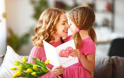 Happy mother`s day! child daughter gives mother a bouquet of flowers to tulips and postcard. Happy mother`s day! child daughter congratulates mother and gives a stock photography
