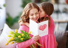 Happy mother`s day! child daughter gives mother a bouquet of flowers to tulips and postcard. Happy mother`s day! child daughter congratulates mother and gives a stock images