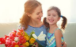 Happy mother`s day! child daughter   gives mother a bouquet of f Stock Image