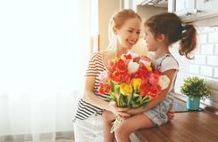 Happy mother`s day! child daughter gives mother a bouquet of f. Happy mother`s day! child daughter congratulates mother and gives a bouquet of flowers to tulips royalty free stock photography
