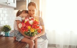 Happy mother`s day! child daughter gives mother a bouquet of f. Happy mother`s day! child daughter congratulates mother and gives a bouquet of flowers to tulips stock image