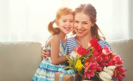 Happy mother`s day! child daughter gives mother a bouquet of f. Happy mother`s day! child daughter congratulates mother and gives a bouquet of flowers to tulips stock photos