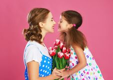 Happy mother`s day! child daughter gives mother a bouquet of flowers on color pink background stock images