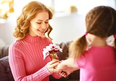 Happy mother`s day! child daughter gives mother a bouquet of flowers and postcard. Happy mother`s day! child daughter congratulates mother and gives a bouquet of royalty free stock photography