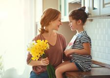Happy mother`s day! child daughter   gives mother a bouquet of flowers to narcissus and gift. Happy mother`s day! child daughter congratulates mother and gives a royalty free stock images