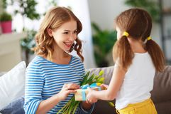 Happy mother`s day! child daughter gives mother a bouquet of flowers to tulip and gift stock photography