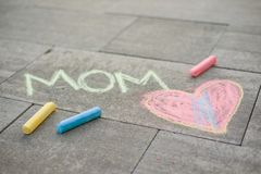 Happy Mother`s Day. Child draws for her mother a picture surprise of crayons on the asphalt. LOVE MOM.  Royalty Free Stock Photography