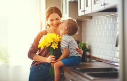 Happy mother`s day! child son gives flowersfor  mother on holiday. Happy mother`s day! child son congratulates mother on holiday and gives flowers stock photography