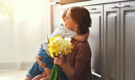 Happy mother`s day! child son gives flowersfor  mother on holiday. Happy mother`s day! child son congratulates mother on holiday and gives flowers stock photos