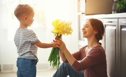 Happy mother`s day! child son gives flowersfor  mother on holiday. Happy mother`s day! child son congratulates mother on holiday and gives flowers stock image
