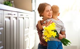Happy mother`s day! child son gives flowersfor  mother on holiday. Happy mother`s day! child son congratulates mother on holiday and gives flowers stock photo