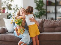 Happy mother`s day! Children congratulates moms and gives her a gift and flowers stock image