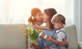 Happy mother`s day! Children congratulates moms and gives her a. Gift and flowers tulips Stock Images
