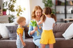 Happy mother`s day! Children congratulates moms and gives her a gift and flowers royalty free stock photos