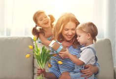 Happy mother`s day! Children congratulates moms and gives her a. Gift and flowers tulips Royalty Free Stock Photos