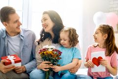 Happy mother`s day. ! Children daughters with dad congratulating mom and give her flowers, gift and card. Family holiday and togetherness royalty free stock images