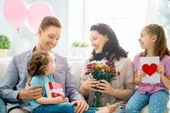 Happy mother`s day. ! Children daughters with dad congratulating mom and give her flowers, gift and card. Family holiday and togetherness royalty free stock image