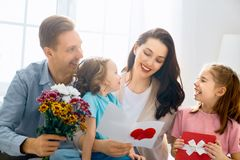 Happy mother`s day. ! Children daughters with dad congratulating mom and give her flowers, gift and card. Family holiday and togetherness stock images