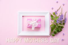 Happy mother`s day concept. Top view of picture frame and gift box with happy mothers day text on pink pastel background. Flat la. Y royalty free stock photography