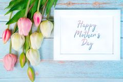 Happy mother`s day concept. white picture frame and flower on wooden background royalty free stock photos