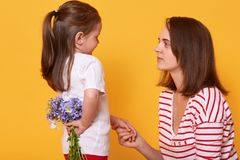 Happy mother`s day! Cute child girl congratulates her mother on holiday and wants to give flowers. Doughter hides bouquet of blue. Florets behinds her back, mum royalty free stock images