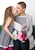 Happy Mother`s Day. Cute little girl giving mom, cancer patient, greeting card, present and bouquet of flowers. Royalty Free Stock Photos