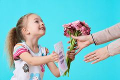 Happy Mother`s Day. Cute little girl giving mom greeting card and bouquet of pink gerbera daisies. Mother and daughter concept. Happy Mother`s Day. Cute little Stock Images