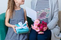 Happy Mother`s Day. Cute Little Girl Giving Mom Greeting Card, Present And Bouquet Of Pink Gerbera Daisies. Mother And Daughter.