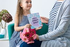 Happy Mother`s Day. Cute little girl giving mom greeting card, present and bouquet of pink gerbera daisies. Mother and daughter. stock image