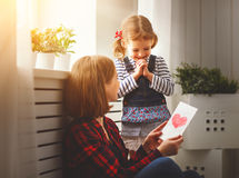Happy mother`s day! Daughter gives her mother an postcard Royalty Free Stock Photography