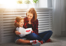Happy mother`s day! Daughter gives her mother an postcard. And hugs Stock Photo