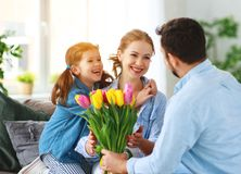 Happy mother`s day! father and child congratulate mother on holiday. Happy mother`s day! father and child daughter congratulate mother on holiday and give royalty free stock photo