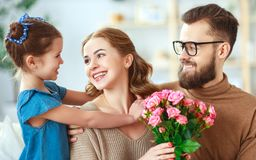 Happy mother`s day! father and child congratulate mother on holiday. Happy mother`s day! father and child daughter congratulate mother on holiday and give stock photos