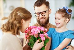 Happy mother`s day! father and child congratulate mother on holiday. Happy mother`s day! father and child daughter congratulate mother on holiday and give royalty free stock photos