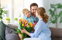 Happy mother`s day! father and child congratulate mother on holiday. Happy mother`s day! father and child son congratulate mother on holiday and give flowers royalty free stock photo