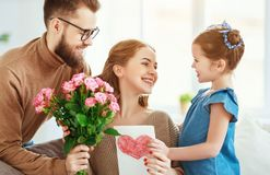 Happy mother`s day! father and child congratulate mother on holiday. Happy mother`s day! father and child daughter congratulate mother on holiday and give stock image