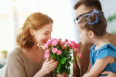 Happy mother`s day! father and child congratulate mother on holiday. Happy mother`s day! father and child daughter congratulate mother on holiday and give royalty free stock image
