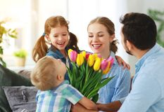 Happy mother`s day! father and children congratulate mother on holiday royalty free stock image