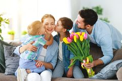 Happy mother`s day! father and children congratulate mother on holiday royalty free stock photography