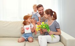 Happy mother`s day! father and children congratulate mother on h Stock Photos