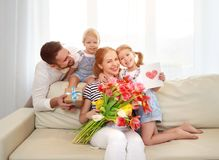 Happy mother`s day! father and children congratulate mother on h. Oliday and give flowers stock image