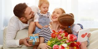Happy mother`s day! father and children congratulate mother on h. Oliday and give flowers stock photo