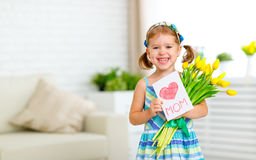 Happy mother`s day! girl with postcard and flowers tulips for mo Royalty Free Stock Photos