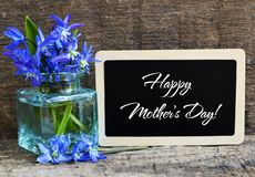 Happy Mother`s Day greeting card with blue spring flowers in a glass vase and chalkboard on old wooden background. Scilla siberica bouquet as a gift for mom royalty free stock photography