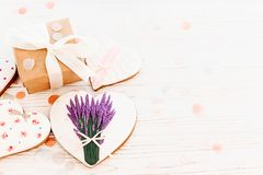 Happy mother`s day greeting card. cookie heart with lavender flo. Wers and craft gift box on white rustic wood background with confetti flat lay. space for text Royalty Free Stock Photo
